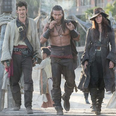 three pirates (two men and a woman) walking along a pier towards the camera