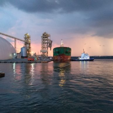 A very dramatic pink sky with dark clouds behind a freighter and tug boat