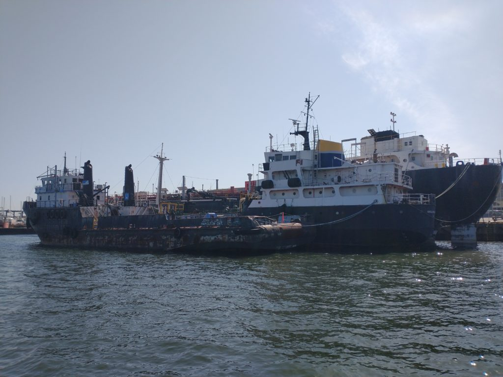 A tug is tied up to a small tanker and a larger ship. All three are derelict.