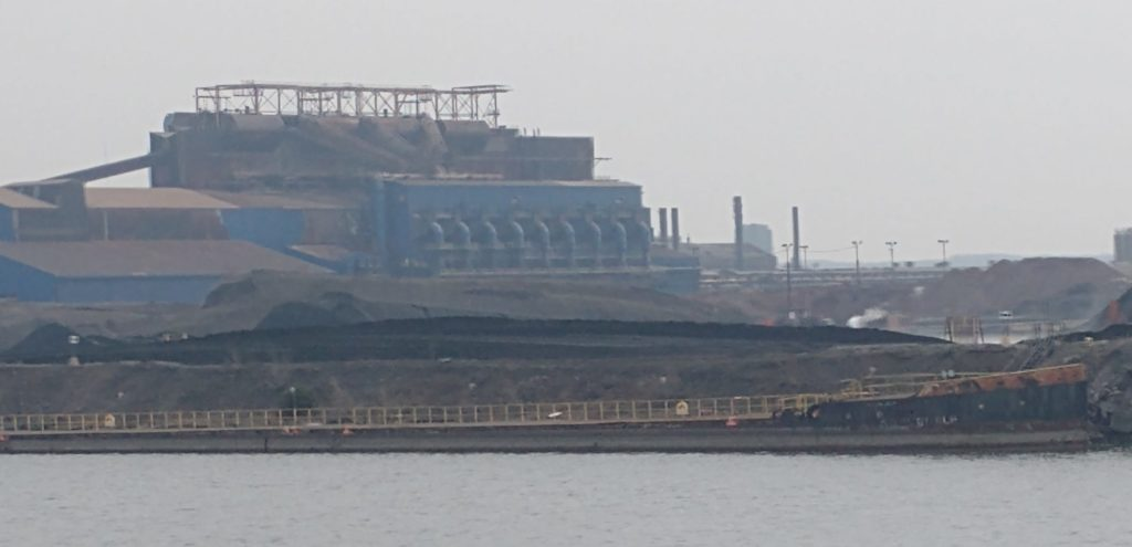 An old freighter has been sunk to be part of a harbour wall, only the hull remains
